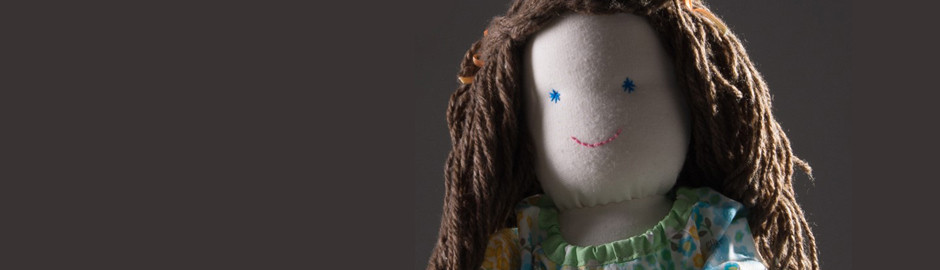 Face of a pale fabric doll with long brown hair