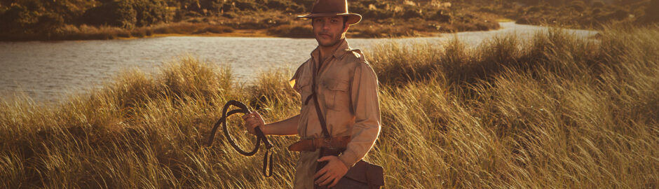 A young man in a tan uniform stands in a golden tussock landscape.